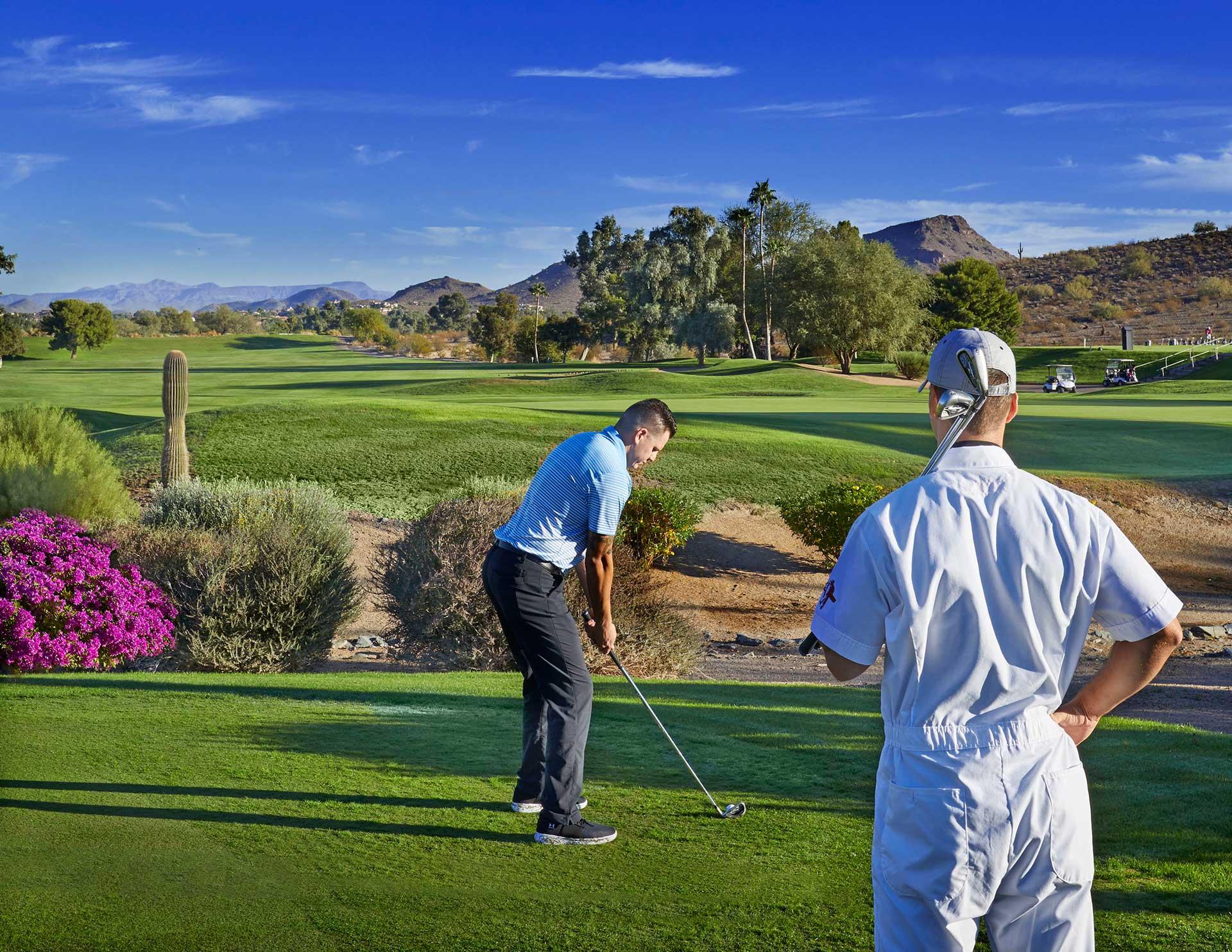 Golfer and caddie on fairway teeing off