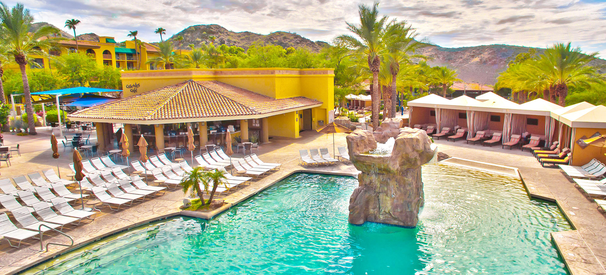 Photo of The Falls Water Village featuring the bar, lounge chairs, sparkling pool, cabanas, palm trees and surrounding mountains
