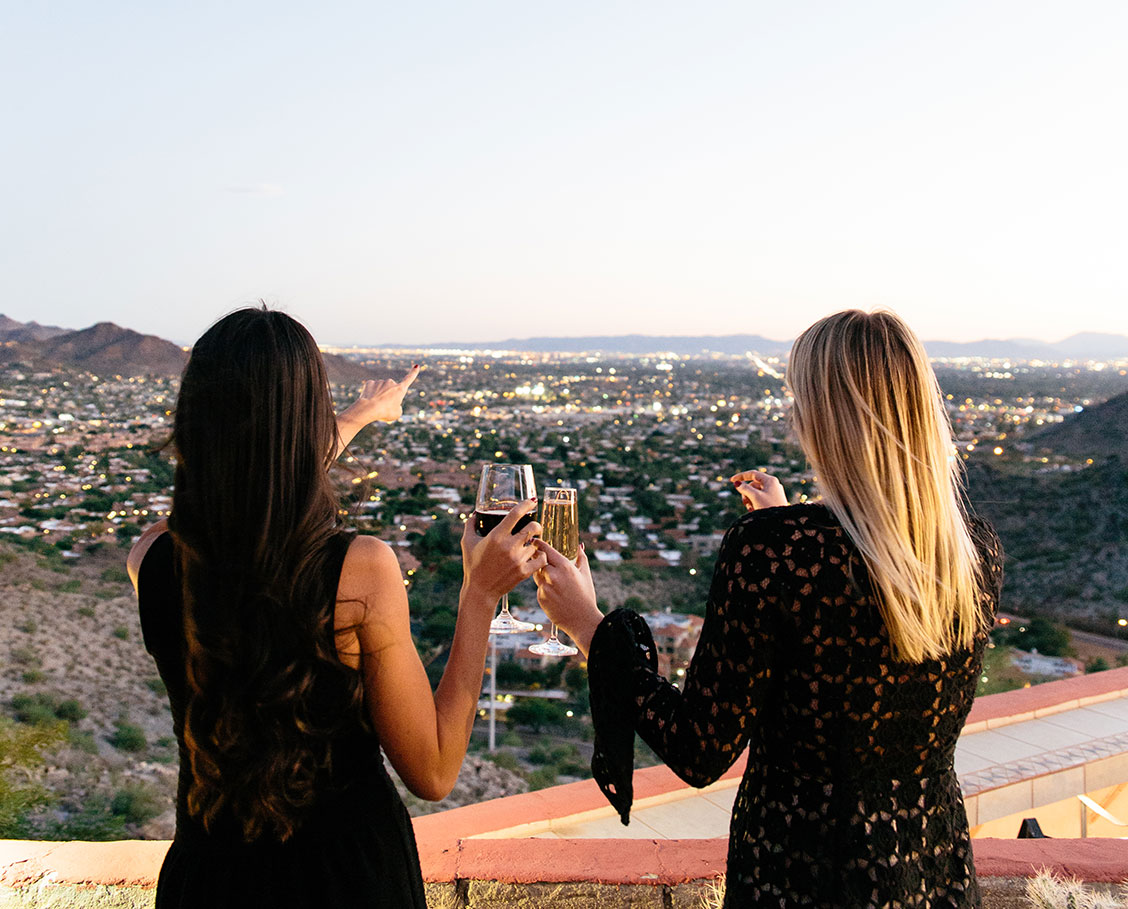 Women friends enjoying wine at dusk while overlooking the twinkling city lights from the patio of Different Pointe of View