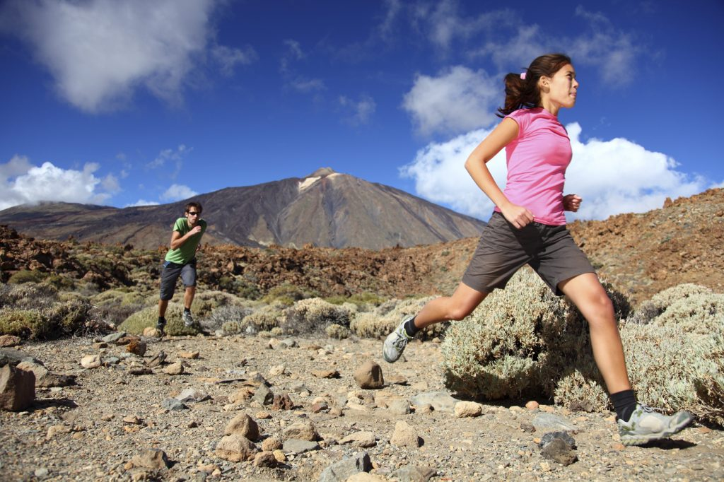 Man and woman running on a desert trail