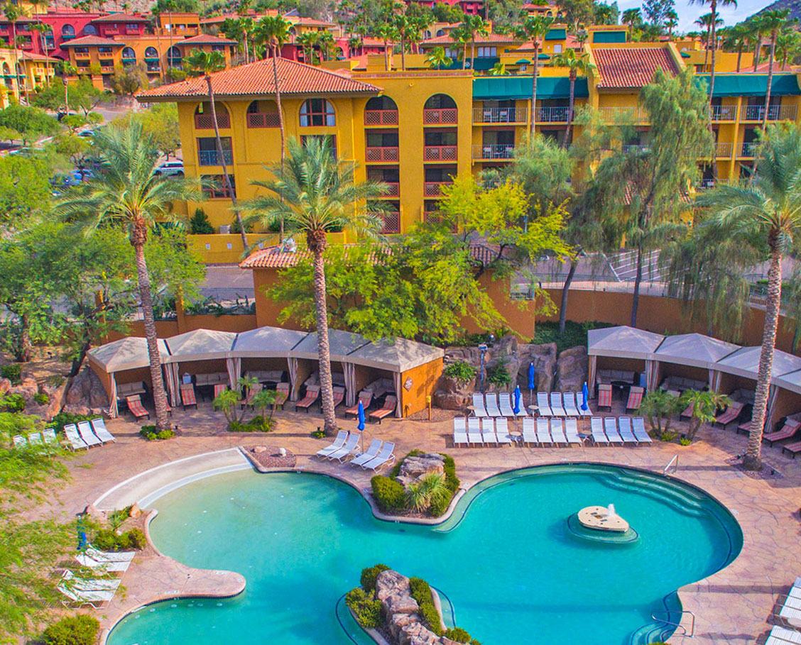 Aerial view of the Grotto Pool at The Falls Water Village with surrounding cabanas, lounge chairs and palm trees and resort buildings and mountains in the background