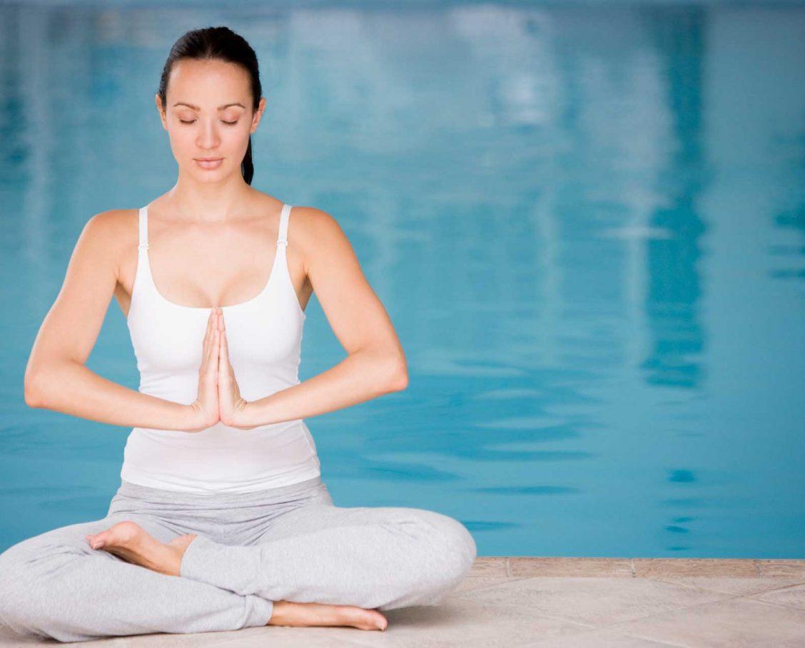 Woman doing yoga and meditating next to a pool