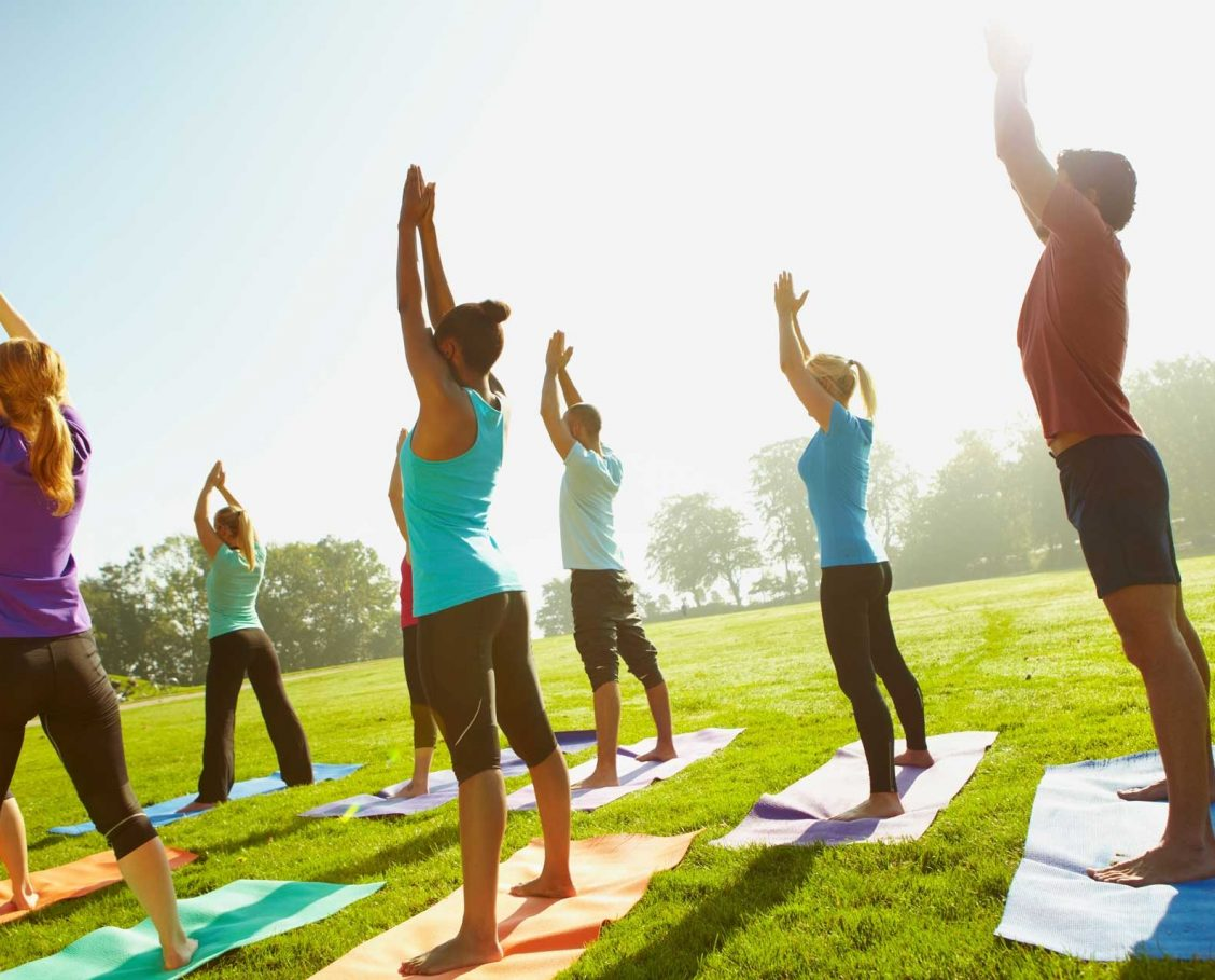 Group on men and women enjoying a yoga class on a golf course