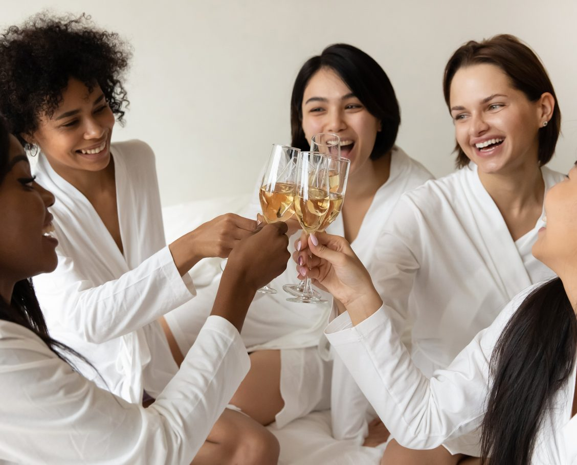 Happy multiethnic young women wearing bathrobes celebrating and clinking glasses on bed