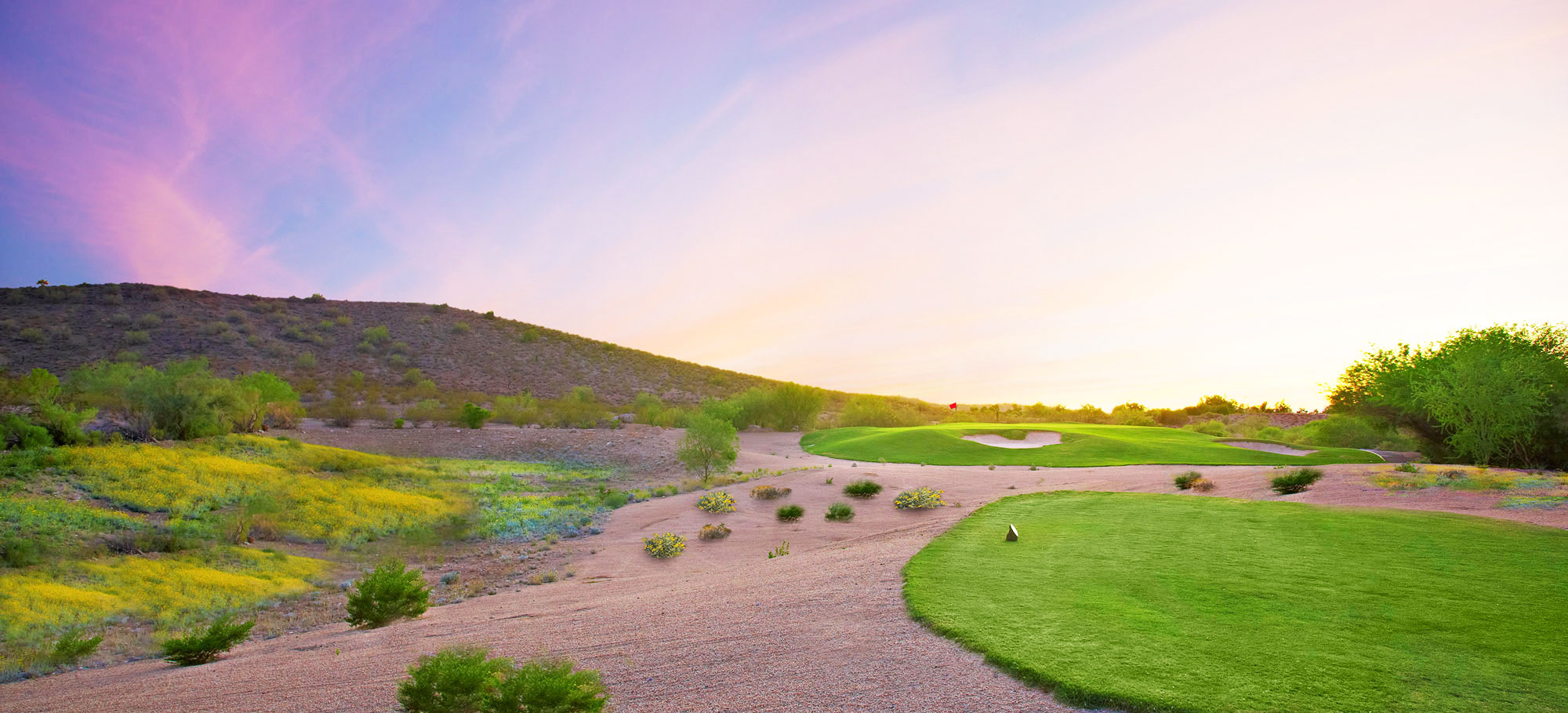 Green golf course at sunrise in the spring