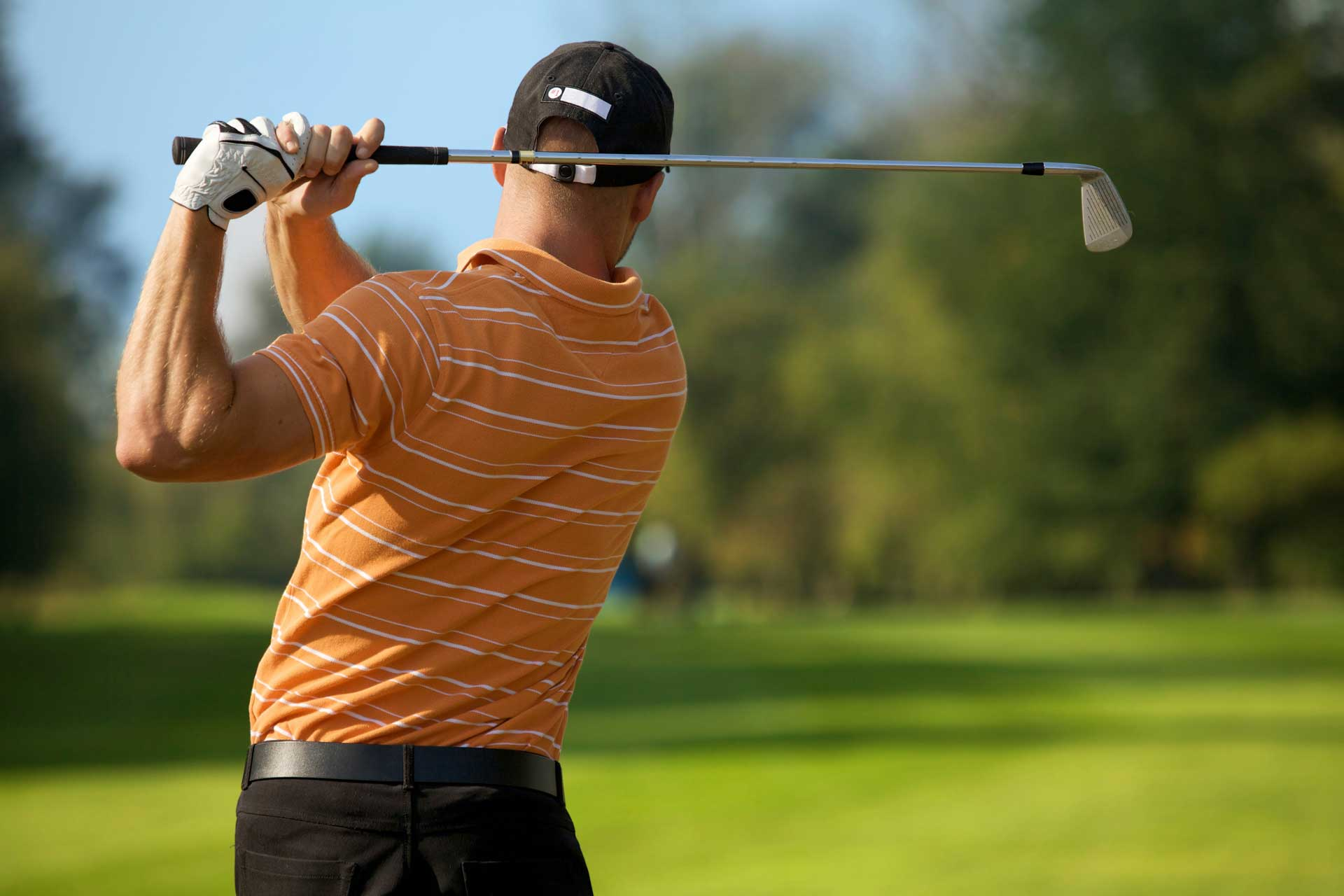 Golfer swinging his club on the fairway
