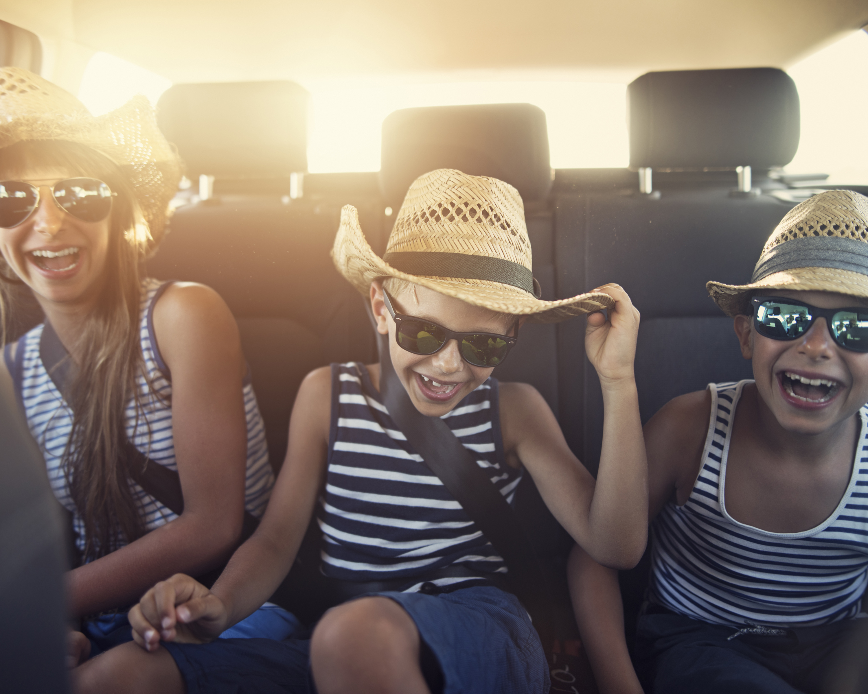 Kids in the back seat of a car enjoying a road trip on sunny day