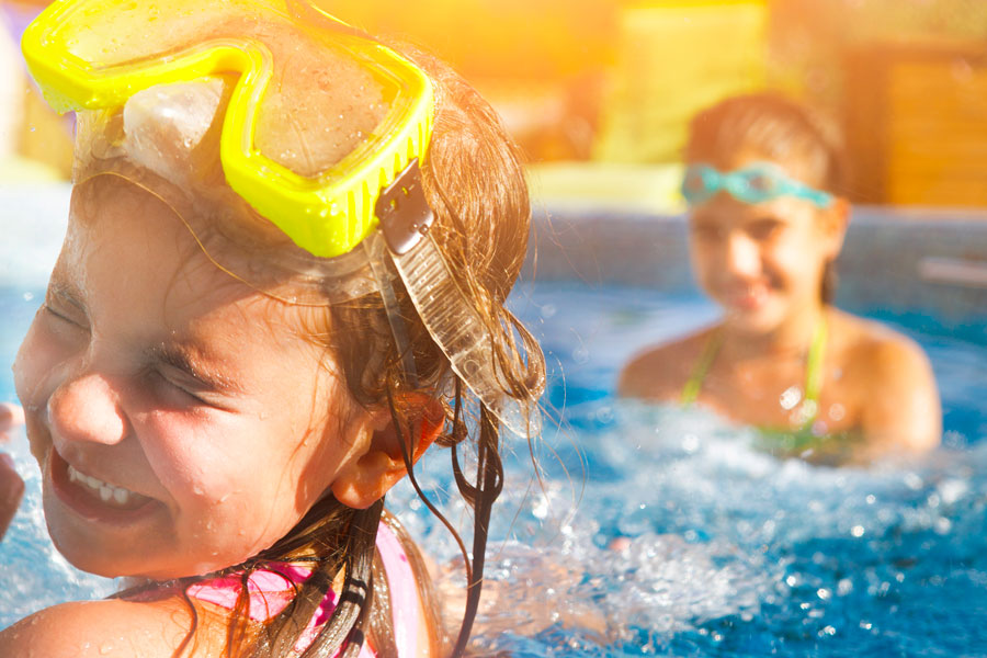 Kids smiling and playing in the pool with swim goggles on their heads