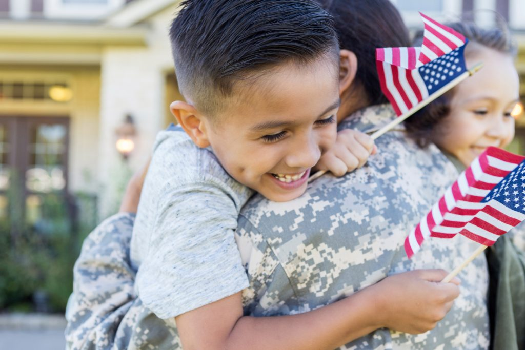 Smiling boy and girl give their soldier mom a big hug on her return home from service. Children are holding small US flags.