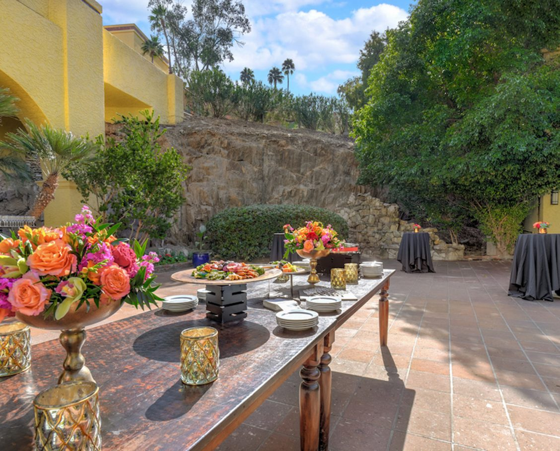 Outdoor courtyard with saltillo-like tile flooring, green trees and shrubs, bright blue skies, a buffet table and several tall reception tables draped in black linen with copper vases and fresh colorful succulent centerpieces