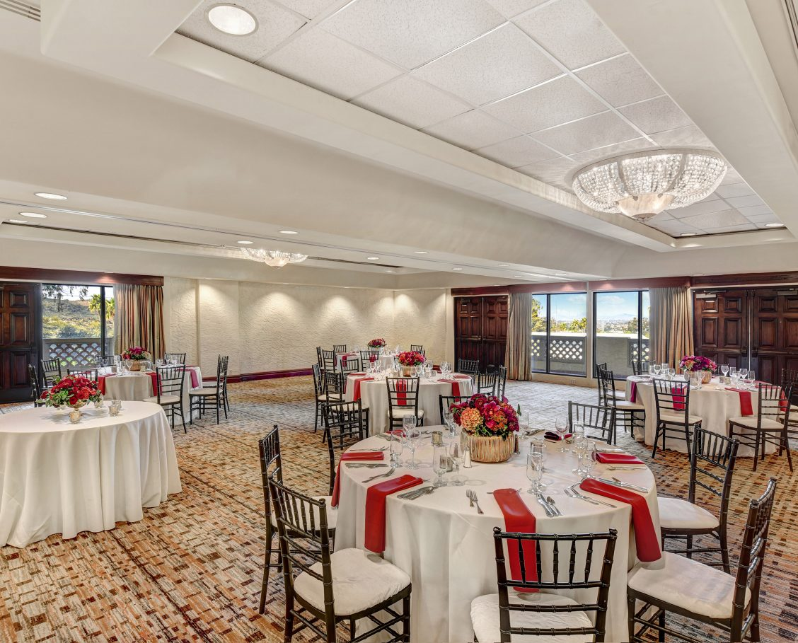 Courtroom with large windows allowing views of surrounding mountains, trees and natural daylight. Room is set for a special event with round tables draped in white linen and berry colored napkins that compliment the beautiful floral centerpieces