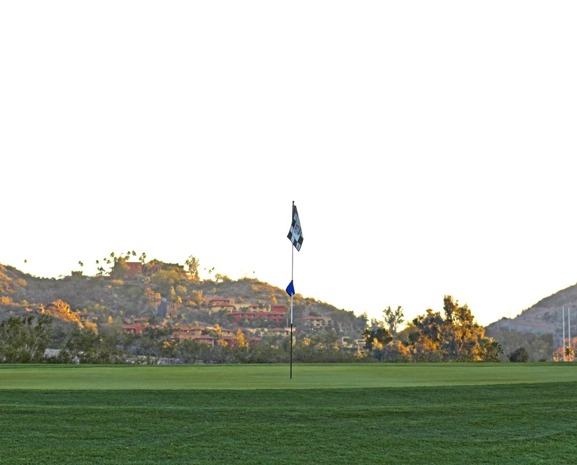 Golf course with checkered flag pin in the foreground and resort buildings nestled into the mountainside in the background