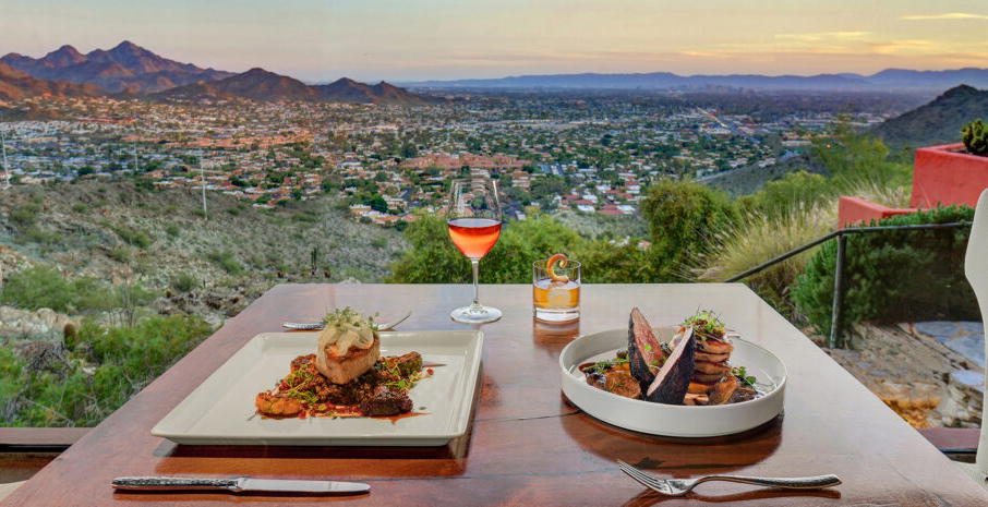 Dinner table with two plated entrees and two cocktails overlooking valley views and mountain peaks at sunset time