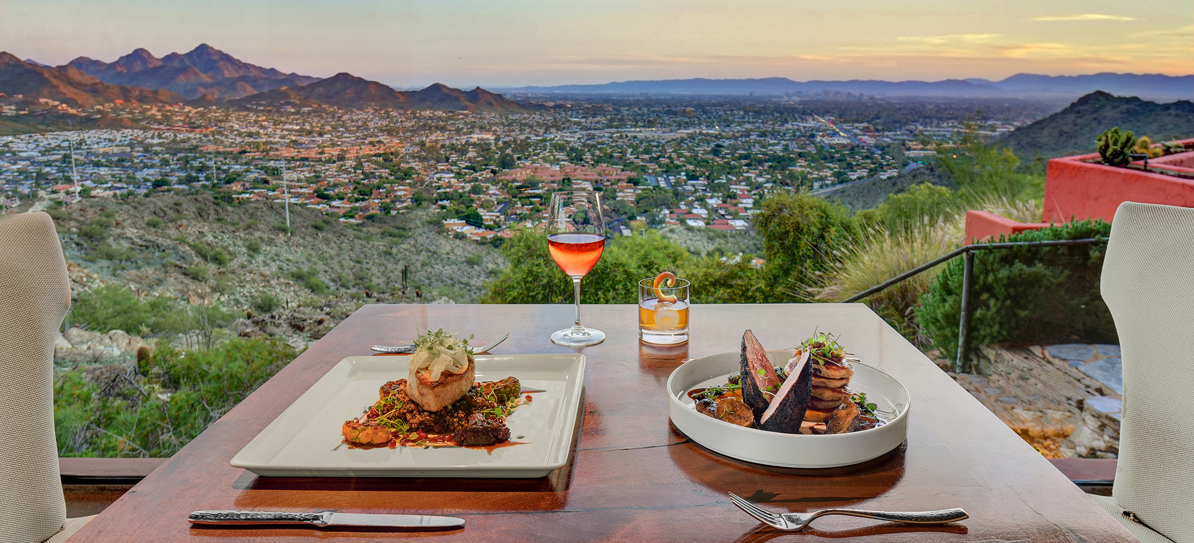 Dinner table set for two, overlooking valley views and mountain peaks at sunset time