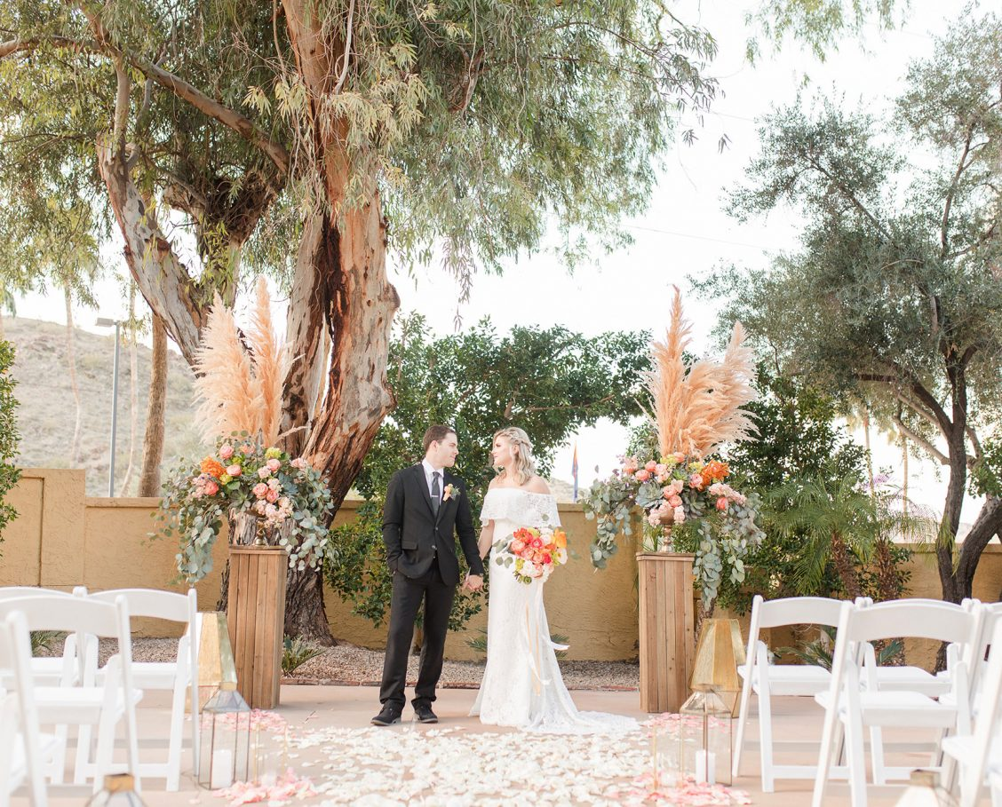Courtyard ceremony setup with bride and groom holding hands and looking at each other