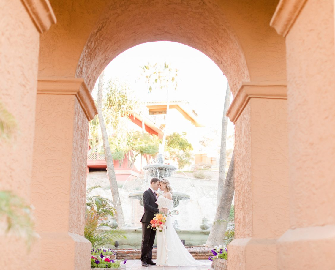 Bride and groom embracing on an outdoor patio next to a large water fountain