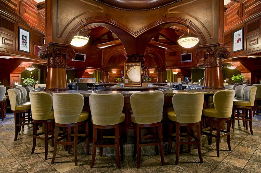 Pointe In Tyme bar seating surrounded by rich mahogany wood accents and two flat screen TVs
