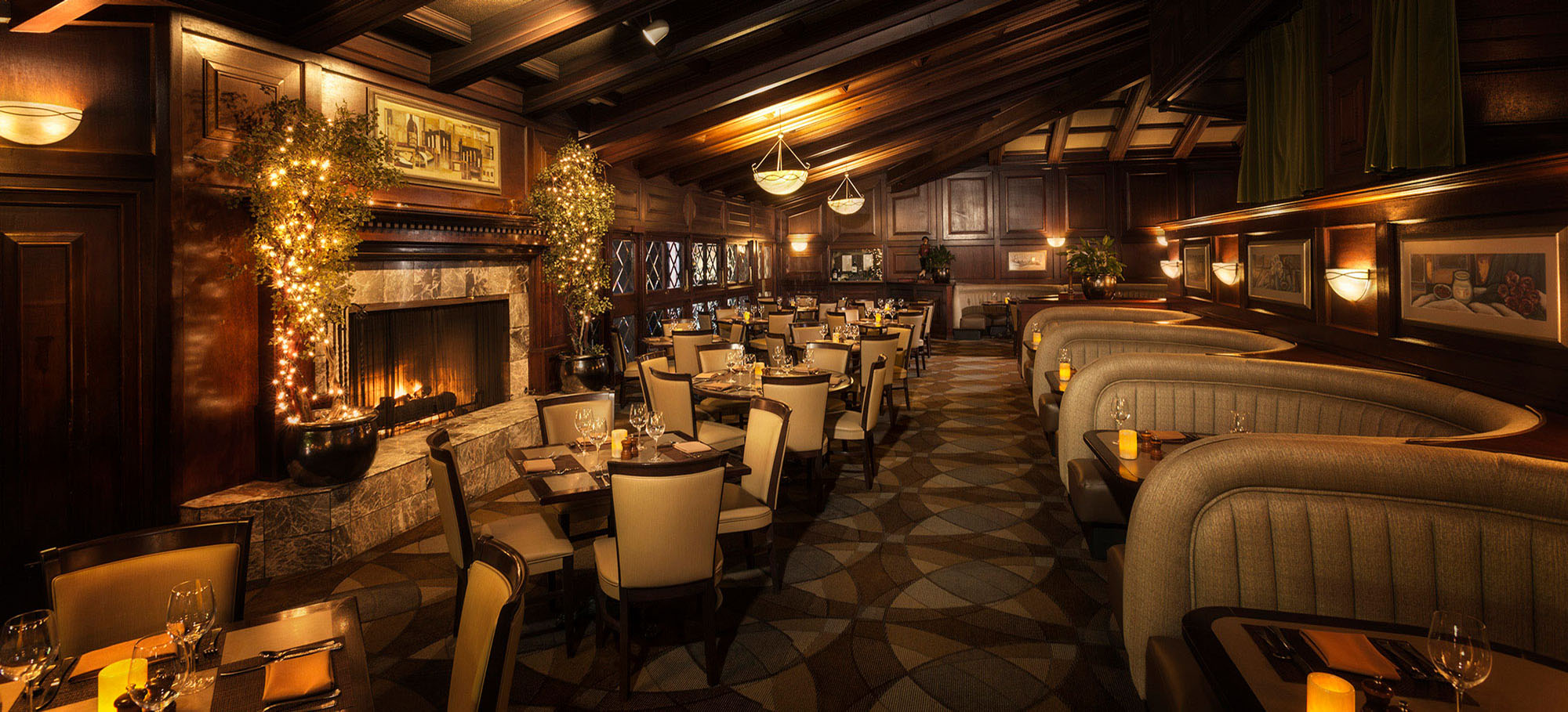 Pointe In Tyme dining room featuring warm lighting, a fireplace, booths and tables