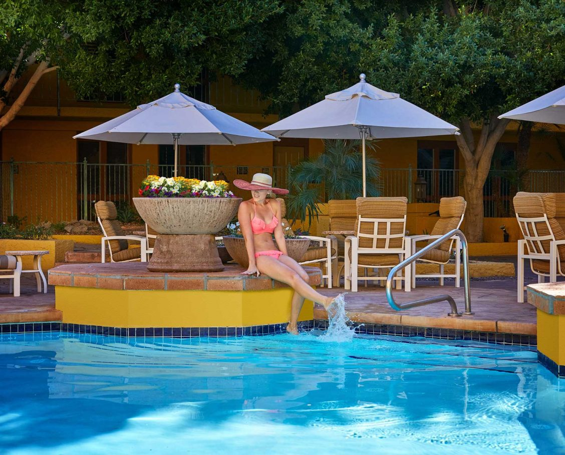 Woman in a bikini sitting on the ledge of the pool with her feet in the water