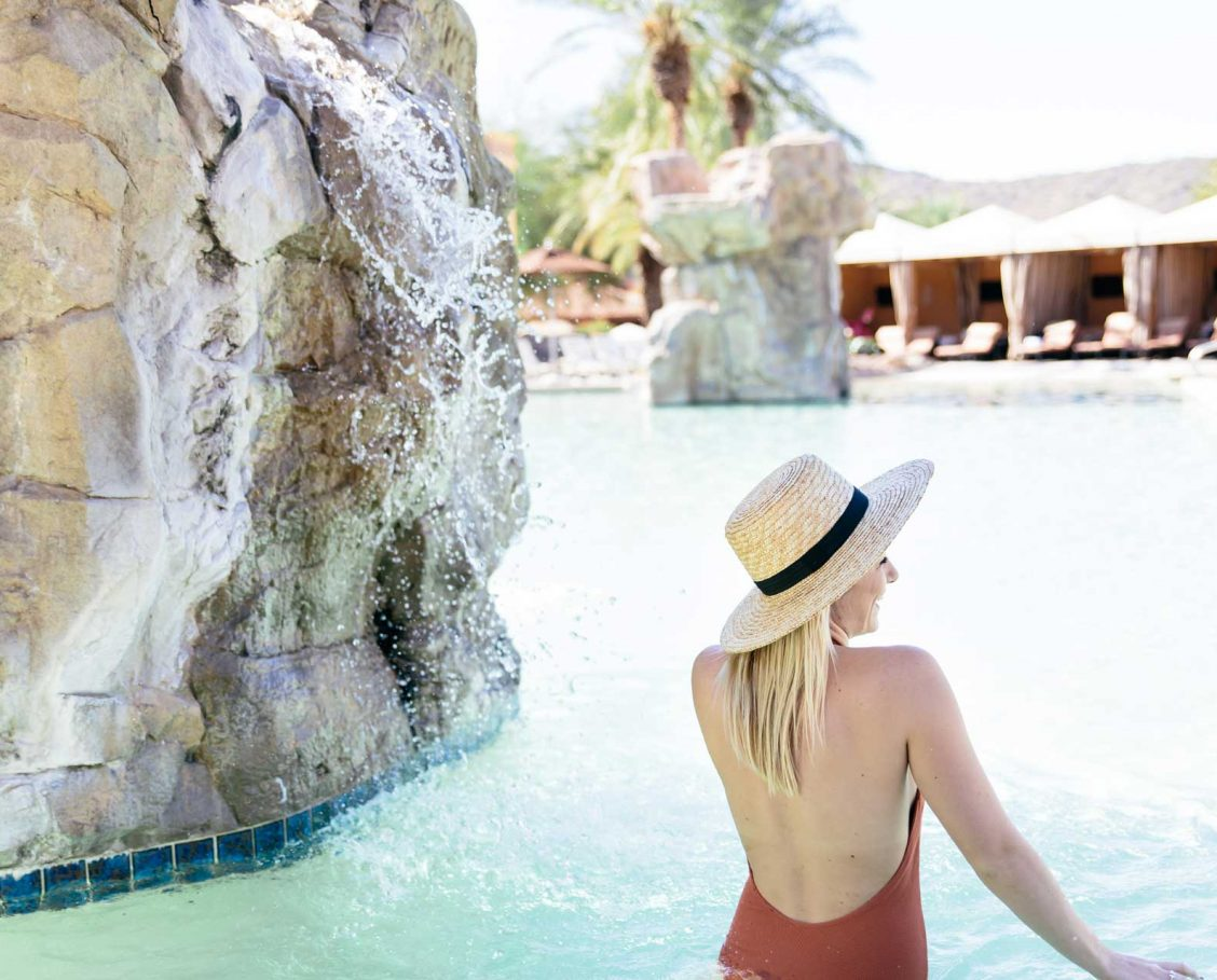 Woman wading in the pool next to a rock waterfall
