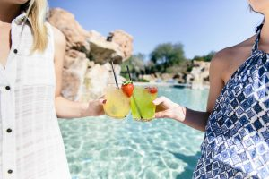 Two women at the pool holding cocktails and toasting each other