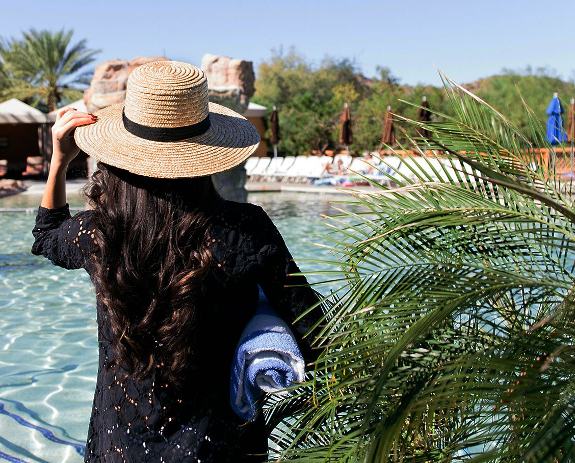 Woman strolling next to the pool with palm trees, cabanas and mountains in the background