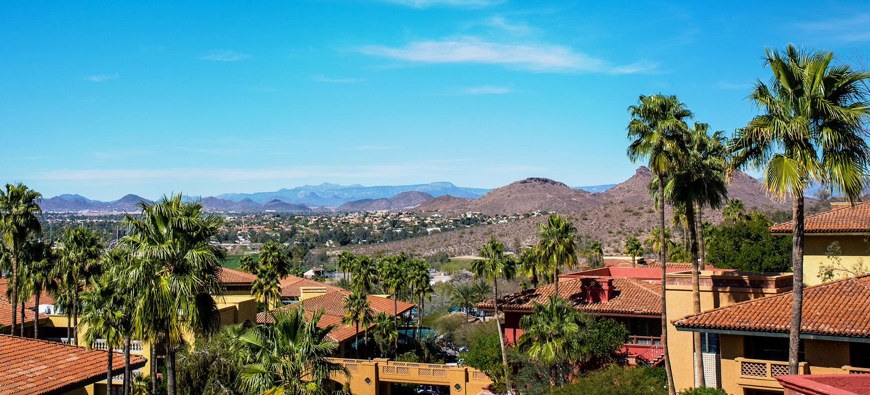 Views of the resort rooftops, mountains and palm trees