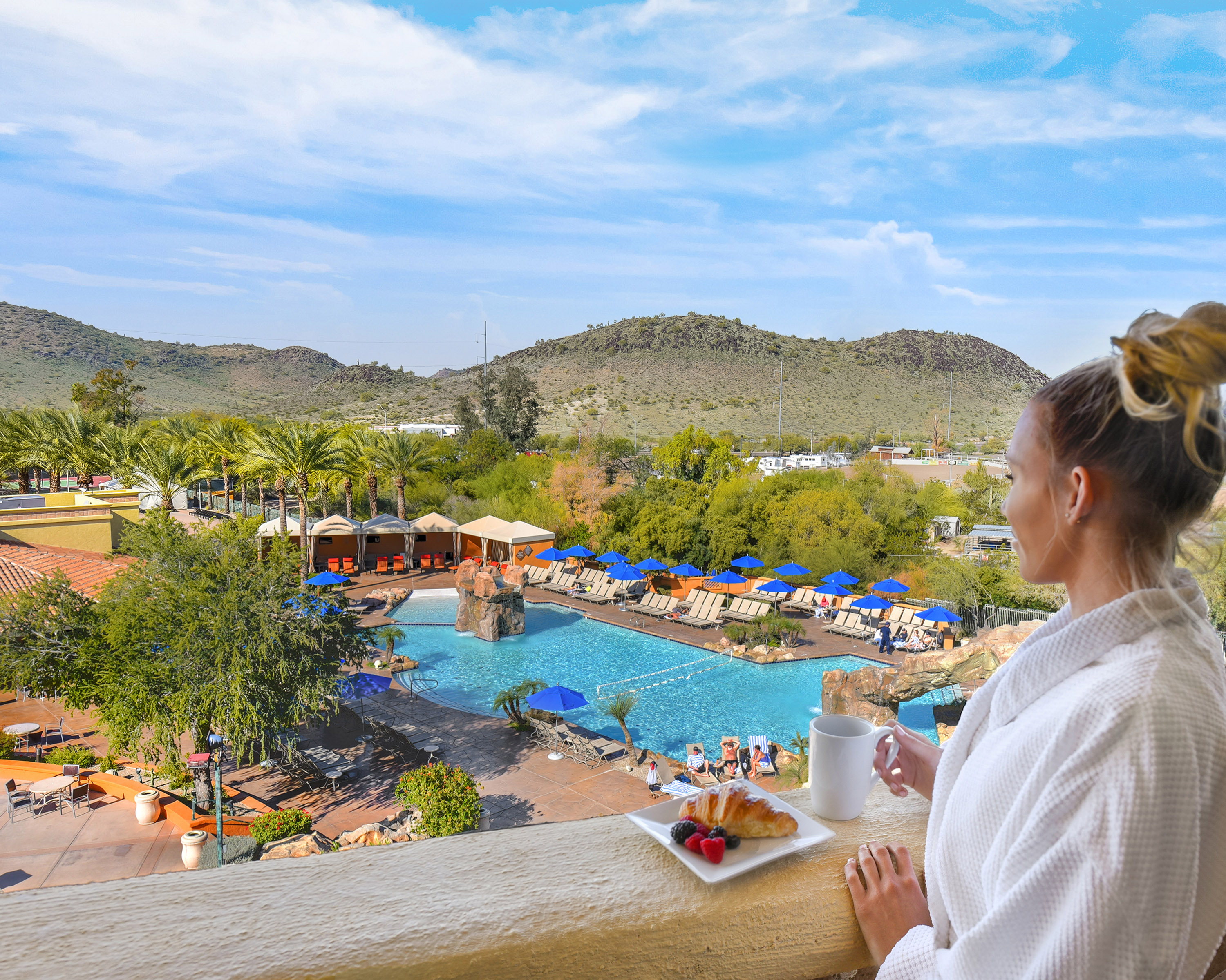 Woman in a cozy bathrobe standing on the balcony of her guest suite with a cup of coffee overlooking a pool and mountains