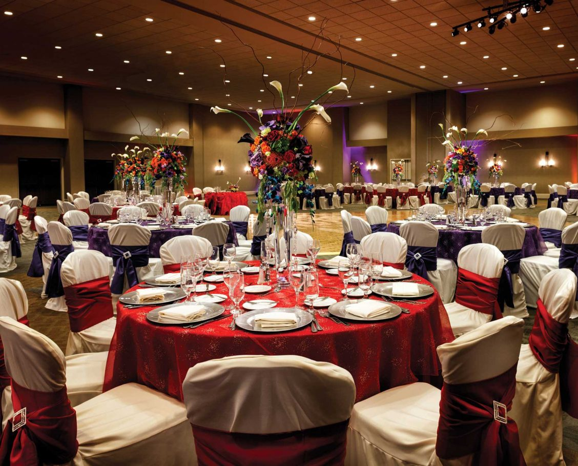 Highland ballroom set for a wedding with vivid linens and colorful floral centerpieces