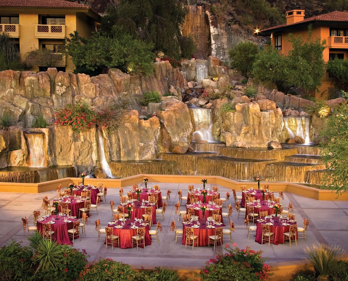 Banquet set-up on an outdoor terrace next to flowing waterfalls