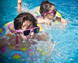 Two young children with sunglasses on splashing and playing in the pool with inflatable water toys